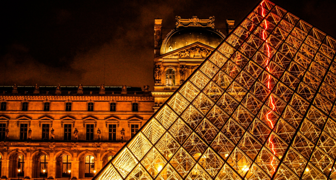 The Louvre museum and glass pyramid illuminated at night