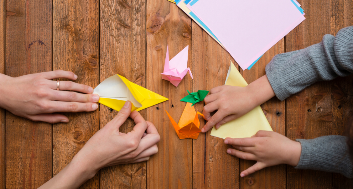 parent and child folding origami birds with brightly coloured paper on a wooden table