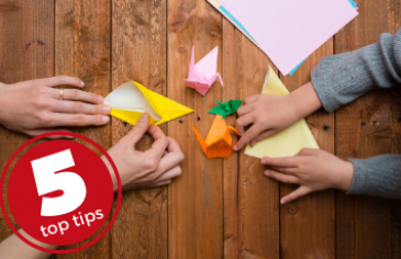 5 top tips origami to make, parent and child folding origami birds with brightly coloured paper on a wooden table
