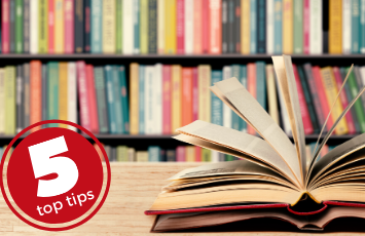 5 top tips: young adult authors to read. An open book on a table in front of a library shelf of multi-colour books