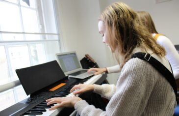 A Red Balloon student playing the keyboard