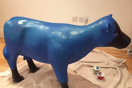 Museum of Cambridge mini-moo, mid-creation by artist Marlis Horgan, showing the night sky painted onto the cow.