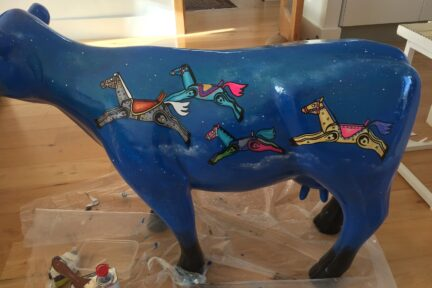 Museum of Cambridge mini-moo, mid-creation by artist Marlis Horgan, showing the night sky painted onto the cow with the rocking horses in full colour.