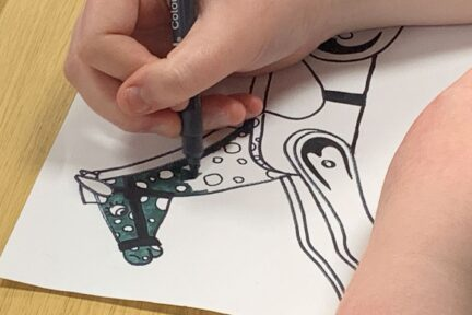 A Red Balloon student colours the head and neck of a rocking horse design on paper