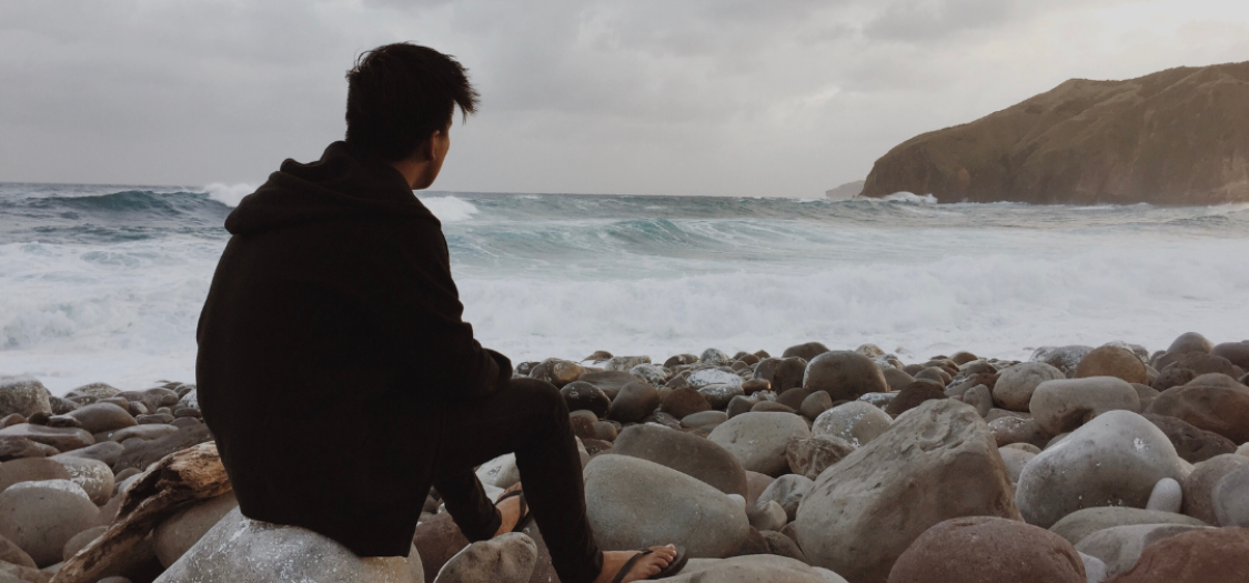 Young man sat on a rock on the shore, looking out to sea on a cloudy day
