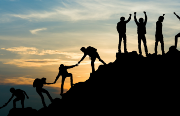 Photo of young people silhouetted against a sunset, helping each other to climb a hill. The photo evokes a feeling of success.